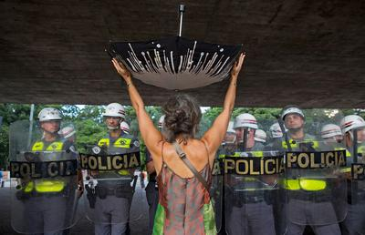 Woman with upturned umbrella at water rationing protest in Sao Paulo (photo credit National Geographic)